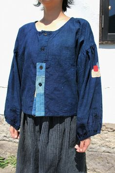 ※日本国内にお住まいの方は「佐々木洋品店公式オンラインショップ」をご覧くださいませ。  こちらは当店で作った洋服、「佐々木印(ササキじるし)」です。  素材は日本の明治時代に使われていた藍染めの古布を使用しております。  特徴的な袖は、肩部分にパフスリーブのようにギャザーを入れ、  さらに袖口部分にも細かいギャザーを入れ、ふわっとした袖にしました。  袖にインパクトがあるので、ボディ部分はシンプルめなデザインですが、  ボタン部分をつぎはぎしており、開けた状態と閉めた状態で印象が変わるように作りました。  古い木綿ですので、多少色あせなどありますが、とても雰囲気の良い藍色です。  身長:157センチ  【実寸サイズ】  肩幅・・・60  袖丈・・・46  胴囲・・・102  着丈・・・51  アームホール・・・38  袖口・・・30  ※多少の誤差が生じる事をご了承くださいませ