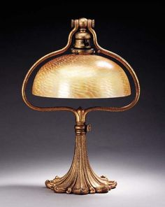A FAVRILE GLASS AND GILT-BRONZE TABLE LAMP   Tiffany Studios, circa 1910   17½in. (44.4cm.) high, 10in. (25.4cm.) diameter of the shade   the gold 'Murano' shade engraved L.C.T. Favrile, the 'bell' base stamped TIFFANY STUDIOS NEW YORK 568