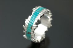 """This ring was made by Christopher Taylor Timberlake from silver cast into the carved-out bone of a cuttlefish that was carved and then hand-fabricated into a ring. Turquoise (Arizona, U.S.) was inlaid and then carved to match the ridges inherent in the casting. Ring is approximately 4-12mm wide with a 3mm wide channel of turquoise."" File Under: For the Poor Sap I Marry"
