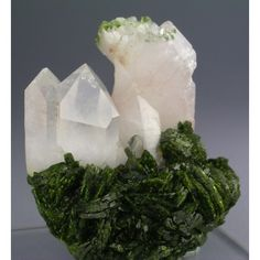 Epidote - A striking combination of clear to white Quartz crystals over a large group of lustrous, rich green Epidotes, from the Hongquizhen quarry in Sichuan, China. / Mineral Friends <3