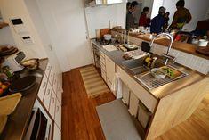 濃く着色したナラ材とそれに縁どられた白いマットな前板のキッチンと食器棚