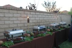 3 8' banquet tables with chocolate brown linens lined up to provide a buffet station to serve Cuban food from Hidden Havana Cafe, located in Newhall, CA. Pineapples, coconuts, and greens to decorate the space.