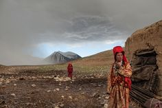 Two girls venture outside their mud hut after a hailstorm at the khan's autumn camp beside the Aksu River. The nomads sometimes stop here for a few weeks between migratory seasons if grass for their herds is too scarce at the summer or winter camps.