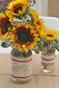 Sunflowers and baby's breath in a mason Jar as rustic wedding centerpieces. Made by your local Riverside CA florist - Willow Branch Florist of Riverside