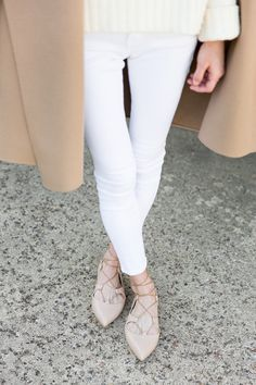 Cream sweater, white pants, camel coat, and nude lace-up flats.