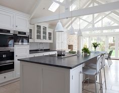 An open plan design, this painted kitchen is light and airy, featuring a large island with seating room and a dining table with French doors behind. Bespoke kitchens available from www.martinmoore.com