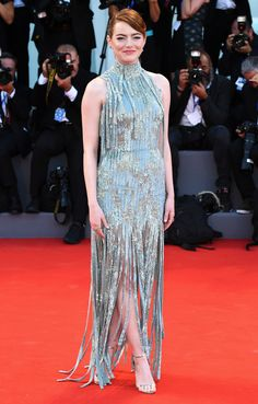 EMMA STONE wears a seafoam sequin Atelier Versace gown with strips of sparkles from her bodice and in the carwash-style skirt, plus silver Jimmy Choo sandals, Selim Mouzannar jewelry and an updo, for the La La Land premiere.
