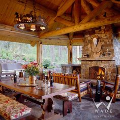 roger wade studio architectural photography of covered patio with dining table and fireplace, private log home, lakeside, montana, by lachance builders and alpine log homes