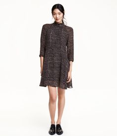 Short dress in patterned chiffon with a ruffled stand-up collar. Buttons at back of neck, open back, and long sleeves with buttons at cuffs. Seam at waist and flared skirt. Lined.