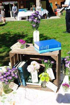 books and wooden crates create a beautiful escort card table