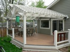 Two-toned composite decking ground-level deck with painted beetle kill pine pergola.