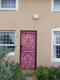the scrolled security gate with a pink front door
