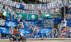 A motorcyclist waits at traffic lights, against the background of election campaign posters and flags of Malaysias ruling National Front, and opposition Pan-Malaysian Islamic Party, on display ahead of the upcoming general elections in Kuala Lumpur, Malaysia.