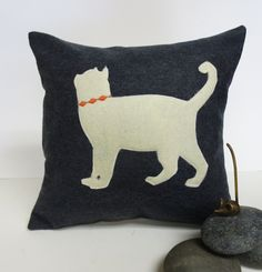 "Grey Felt Pillow with Ivory Cat Felt Applique. Grey Felt Pillow / Cover with Ivory Felt Cat Silhouette ~*Construction*~ The front of the pillow is fabricated out of a grey felt. At the center there is a profile of a cat appliqued in ivory eco friendly felt. The cat has a orange embroidery collar. The back is black and ivory ticking stripe cotton with a exposed black zipper ~Dimensions & Other Info~ Cover accommodates a 12"" x 12"" pillow insert / you can either provide your own or purchase..."