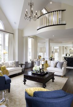 The more formal living room of the home, in navy, gold, and cream with light gray accents. The soaring ceiling has a large iron chandelier hanging far above the furniture.