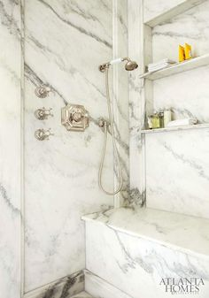 Incredible shower enclosure with recessed paneled marble interior! Montclair Danby Marble from Vermont is used to create paneled walls, a shower bench and slim recessed shelving for shower essentials.