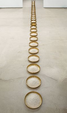 """Wolfgang Laib [Germany] (b 1950) ~ """"The Rice Meals"""", 1998. Brass plates, rice, and hazelnut pollen (936 x 25 cm)"""