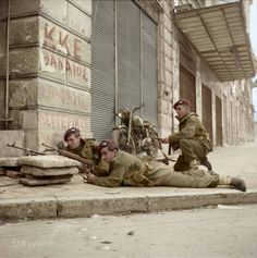 """Paratroopers from 5th (Scots) Parachute Battalion, 2nd Parachute Brigade, L/Cpl D Fairbanks, Pte J E Gregory and Cpl W Lannery (kneeling), take cover on the corner of Kriezotou and Panepistimiou Streets in Athens during operations against members of ELAS, 6 December 1944.  """"..... where the old Hotel King's Palace was located."""""""