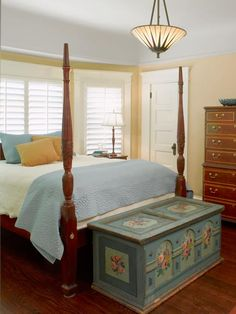 This master bedroom has a coved plaster ceiling original to the 1907 Craftsman house. A bay window lets the sun in and an antique French chest provides extra storage.