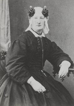 Geertje Corver uit Schagerbrug, gekleed in West-Friese streekdracht. Boven de uiteinden van het oorijzer draagt ze een paar grote lokken vals haar. 1865-1875 #NoordHolland #WestFriesland