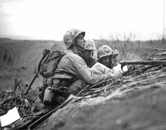 During the invasion on Iwo Jima, in February 1945, advancing U.S. troops spot a Japanese machine gun nest ahead of them. One of the men is establishing its location on the map, so they can forward the information to artillery or mortar units to wipe out these positions.
