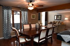Contemporary-style formal dining room with classic touches. Includes ceiling fan, wood floors, blue and white curtains. Wood table with white upholstery and silver vase.