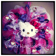 Hello Kitty wreath made with pink and purple broad ribbon and hello kitty accents with her face in the middle.