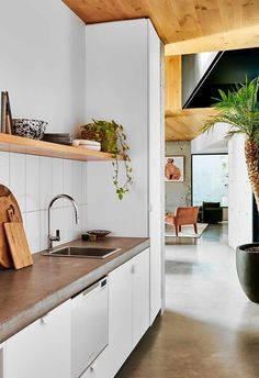 The concrete benchtop in the butler's pantry of this coastal home complements the concrete flooring, while a white splashback and a timber-panelled ceiling provide contrast.