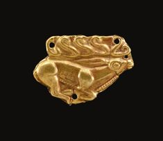 A SCYTHIAN GOLD APPLIQUÉ   circa late 5th century b.c.   The sheet plaque die-formed in the form of a stag in right profile, with multiple branched, curling antlers, pierced for attachment five times along the edges
