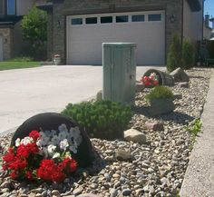 Drawing the eye away from a utility box can be more effective than trying to hide it. These attractive rain barrels do just that. The river rock makes for a great dry river bed collecting the downspout water from between the homes in times of heavy rain.