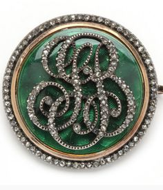 Victorian 18KT Diamond and Enamel Initial Brooch  designed in circular form of green guilloche enamel over gold and with bead set rose cut diamond initials in a scroll pattern and accented to the border with rose cut diamonds, the (141) diamonds approximately .70 total carats