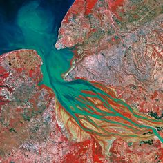 Spectacular Views of Earth from Space | DiscoverMagazine.com | Bombetoka Bay, Madagascar | Alluvial islands stretch out in the direction of the current, preceded and extended by sandbanks; they are partially covered by mangrove trees, seen in red in this image.  In the surrounding area, the heavily cleared forest gives way to brush and cassava and rice plantations.