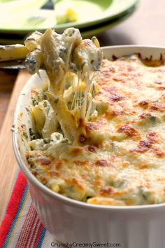 Cheesy Spinach Dip Chicken Pasta - your new favorite dinner! Spinach dip and pasta get together to create one cheesy and creamy dish!