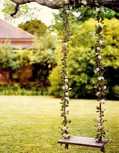 Dainty outdoor tree swing with flowered vines.