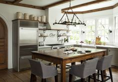 Another view of rustic kitchen, note trim, wood, white, steel, light, window, gray, table, island.