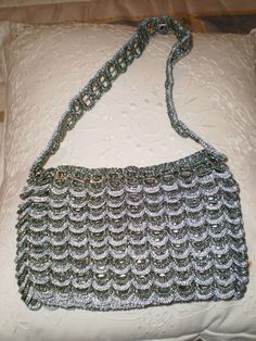 This site has many pictures of Bags made with drink tabs and crochet.  Some close ups show enough that I can figure it out.
