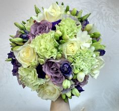 brides handtied bouquet of green carnations, avalanche roses, purple  lissianthus, white freesia and memory lane roses.