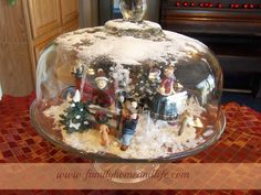 Family Home and Life: Easy Christmas Decorating Idea.  Use a glass covered cake stand as a tabletop decoration using dollar store figurines and artificial snow.