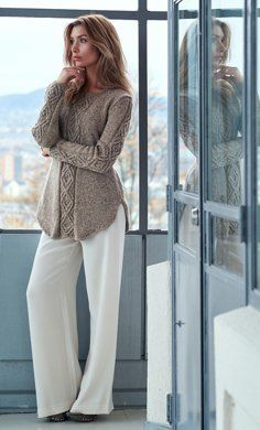 A shadow diamond cable dominates this a-line sweater with a curved flattering hem. I-cord bands frame the bottom of the sweater, while garter stitches mark the sides and the round neckband. The sweater, with or without the cowl to dress it up, make the outfit ideal for the Goddess of good luck; Oydis. The body of the sweater is knitted flat, while the sleeves and the cowl, are knitted in the round. A fine tweed yarn is held together with an alpaca lace yarn, with a chain construction, to…
