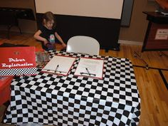 Driver registration to check their cars in. Signs were made by spray painting canvas boards red, cutting out the words with Silhouette, checkered duck tape along the bottom, checkered flag sticker to the Driver Registration sign. Do the same with clipboards- cover pens in checkered duck tape