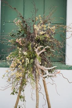 Large Swamp Teepee Arrangement with spanish moss, flowering branches, and antlers.