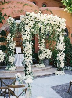 For an elegant ceremony, cover a wedding arbor with an abundance of flowers ~ http://www.stylemepretty.com/2016/02/04/black-tie-secret-garden-wedding/