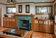 typical Arts & Crafts fireplace wall. Love the symmetry,wide windows, built in storage, display area and materials (tile and wood).