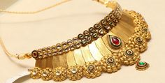Very stylish antique gold choker necklace with kundan setting. The green and white kundans adorn the top and bottom part is embellished with floral motifs.