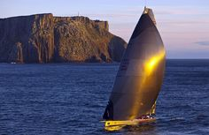 """Australian supermaxi """"Wild Oats XI"""", skippered by Mark Richards, is seen sailing past Tasman Island at sunrise as it approached the finish line of the 64th annual 628-nautical mile Sydney Hobart Yacht Race on December 28, 2008. """"Wild Oats XI"""" won Australia's premier blue water classic for a record fourth consecutive year in an elapsed time of one day, 20 hours, 34 minutes and 14 seconds. (DANIEL FORSTER/AFP/Getty Images) #"""