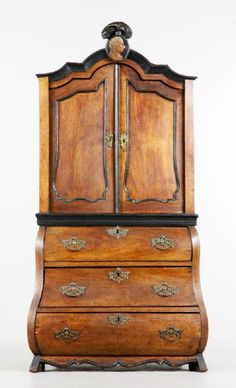 18th century German diminutive bombe style cabinet, with a carved medallion head crest