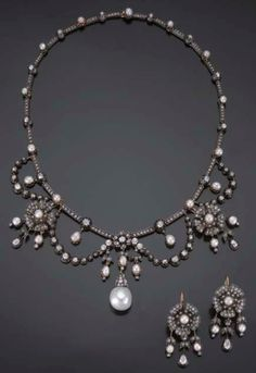 An antique diamond and pearl demi parure, circa 1860. Consisting of a necklace and a pair of earrings. The neckalce with floral and swag motifs, set with diamonds and pearls, suspending a fine baroque pearl, mounted in silver and gold; accompanied by a pair of earrings set with diamonds and pearls. #antique #necklace #earrings