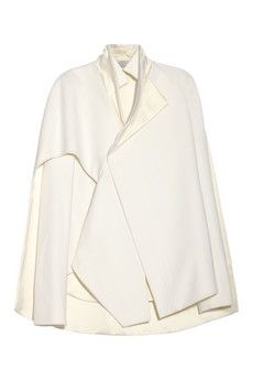 Esteban Cortazar's clean, architectural mindset produced this ivory wool-blend jacket that exudes an angular elegance. A crisp cape overlay demonstrates his focused ingenuity.