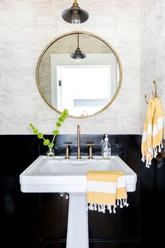 a black and white bathroom with pedestal sink