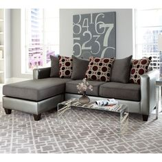 This 2-piece sectional is upholstered in a pewter and grey bi-cast and microfiber fabric. It features abstract print scatter back pillows, generous and plenty of style. Ottoman and chaise pillow can be placed on either side to make a left or right chaise.